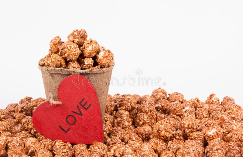 Chocolate caramel popcorn in paper bucket on white background. Popcorn and red heart. royalty free stock images