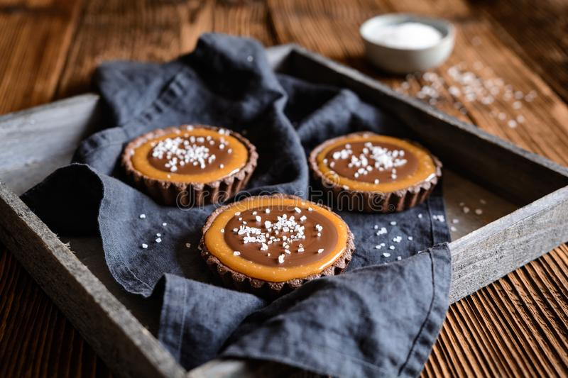 Chocolate caramel tartlets studded with salt stock photo