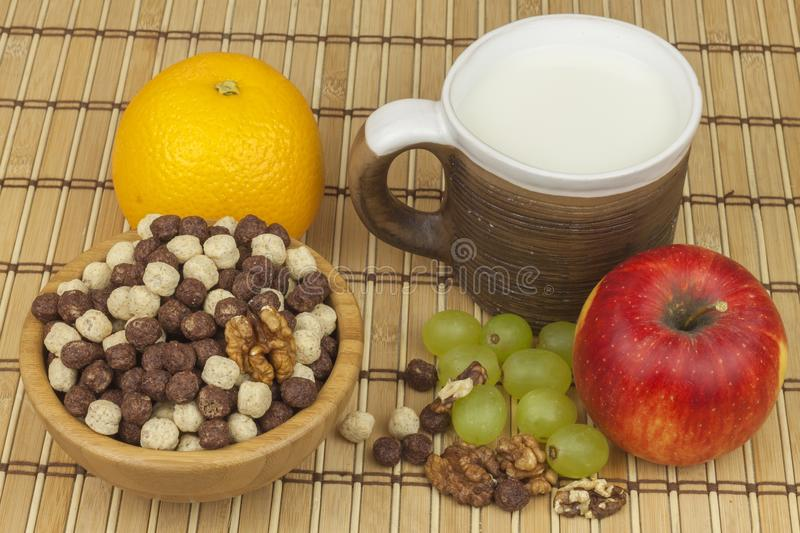 Chocolate cereal balls in a bowl of bamboo. Healthy breakfast with fruit and milk. A diet full of energy and fiber for athletes stock photography