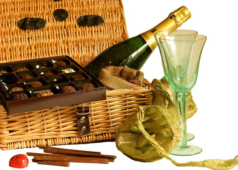 Chocolates and champagne hamper. Isolated image. Assorted chocolates and champagne hamper with open box and wine glasses stock images