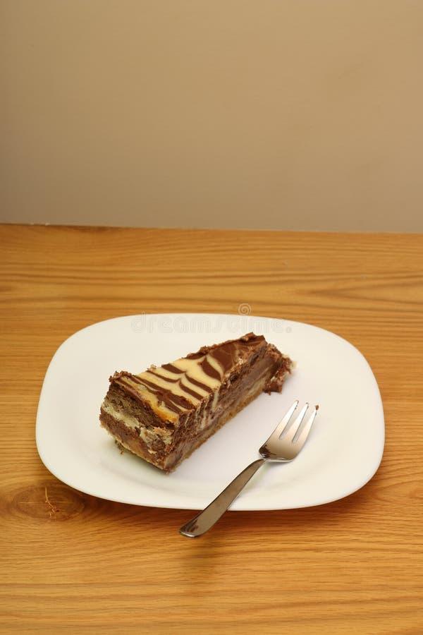 Chocolate & cheese cake slice. On wooden stock photo