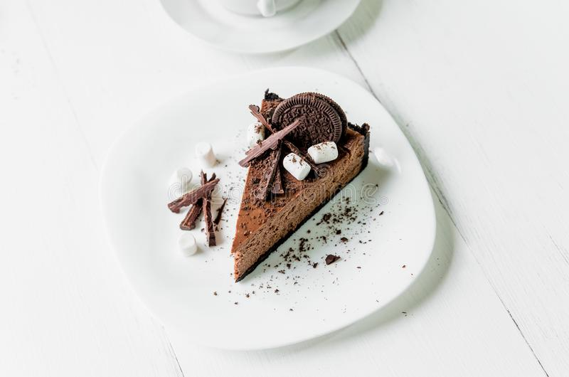 Chocolate cheesecake with pieces of chocolate, cookies and marshmallow on a white plate stock image