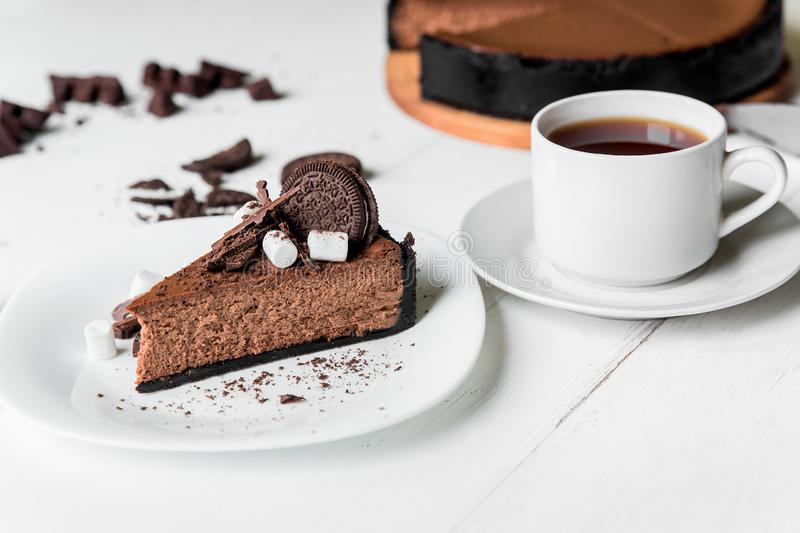 Chocolate cheesecake with pieces of chocolate, cookies and marshmallow on a white plate royalty free stock photography