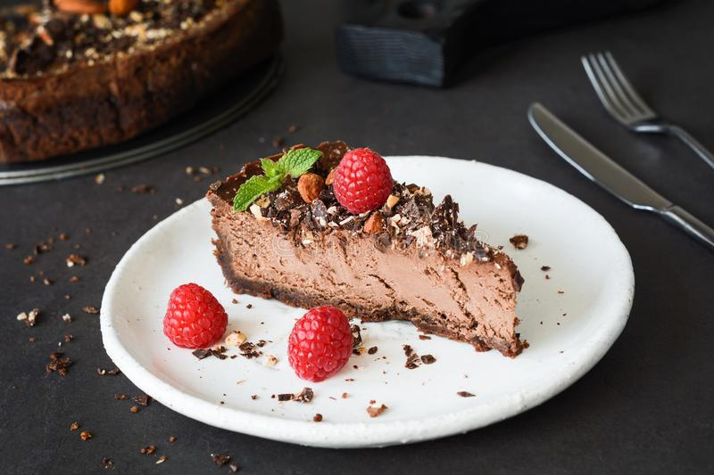 Chocolate cheesecake with raspberries, nuts and mint leaf on white plate. stock photos