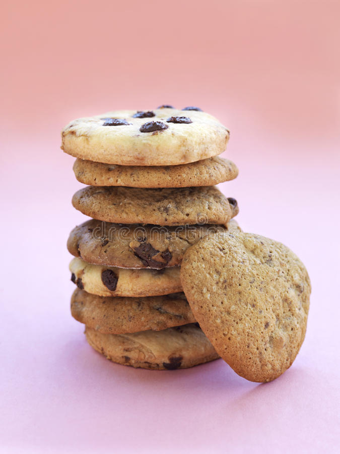 Chocolate chip and almond cookies stacked. On a pink background stock photography