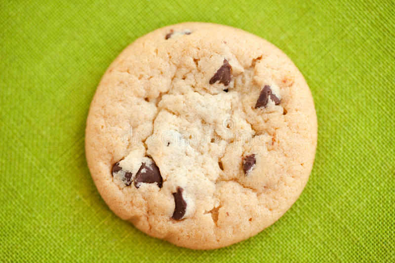 Chocolate chip cookie. A chocolate chip cookie on a green fabric background stock images