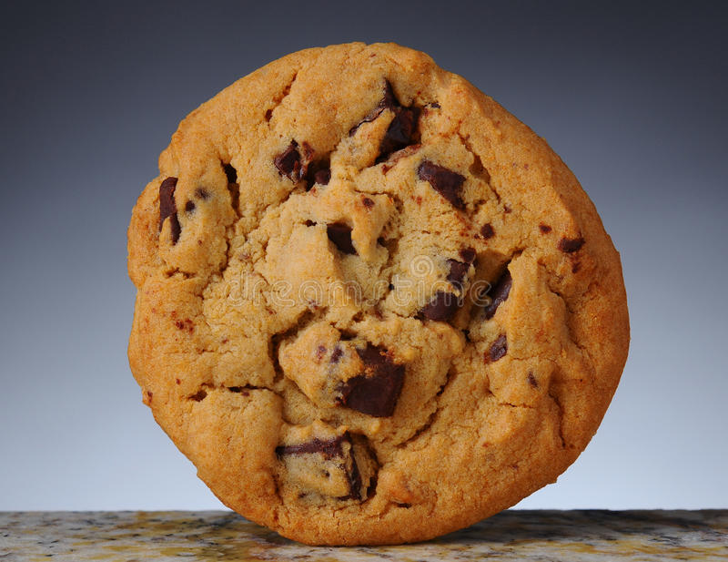 Chocolate Chip Cookie. Closeup of a Chocolate Chip Cookie standing on its side on granite counter top. Light to dark gray background stock photography