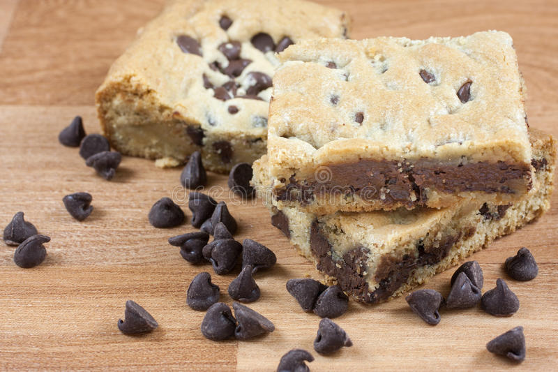 Chocolate Chip Cookie Bars. On a wooden surface with chocolate chips in the forground stock photography