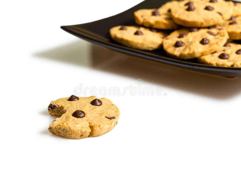 Chocolate chip cookie with a bite and pile of cookies in a plate royalty free stock images