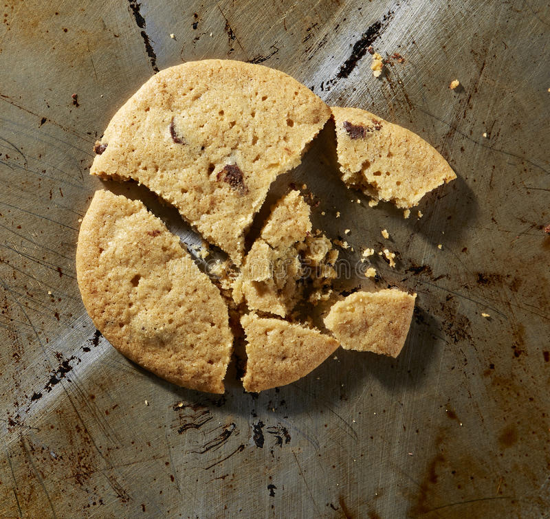 Chocolate Chip Cookie. Broken chocolate chip cookie on baking sheet stock photography