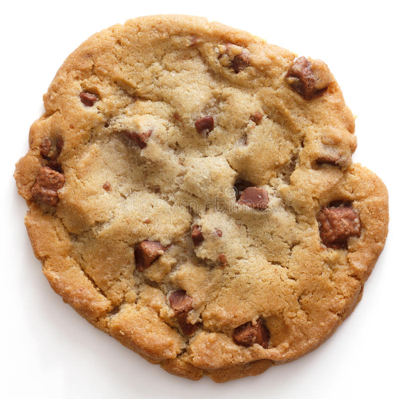 Chocolate chip cookie. Large light chocolate chip cookie on a white surface shot from above stock image