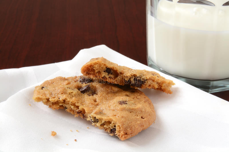 Chocolate chip cookie and milk. A fresh baked chocolate chip cookie broken in two with a glass of milk royalty free stock images