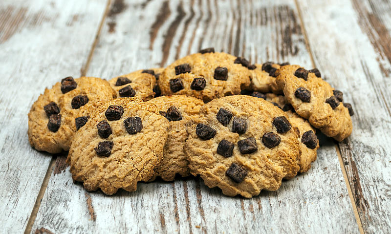 Chocolate chip cookie. Surrounded by rustic background royalty free stock photos