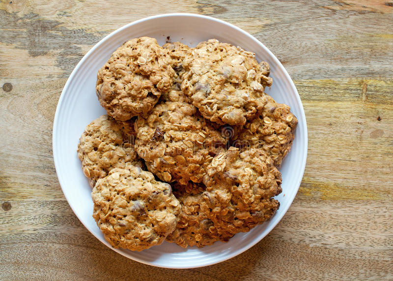 Chocolate Chip Cookies. Arranged on white plate on wooden table royalty free stock photography