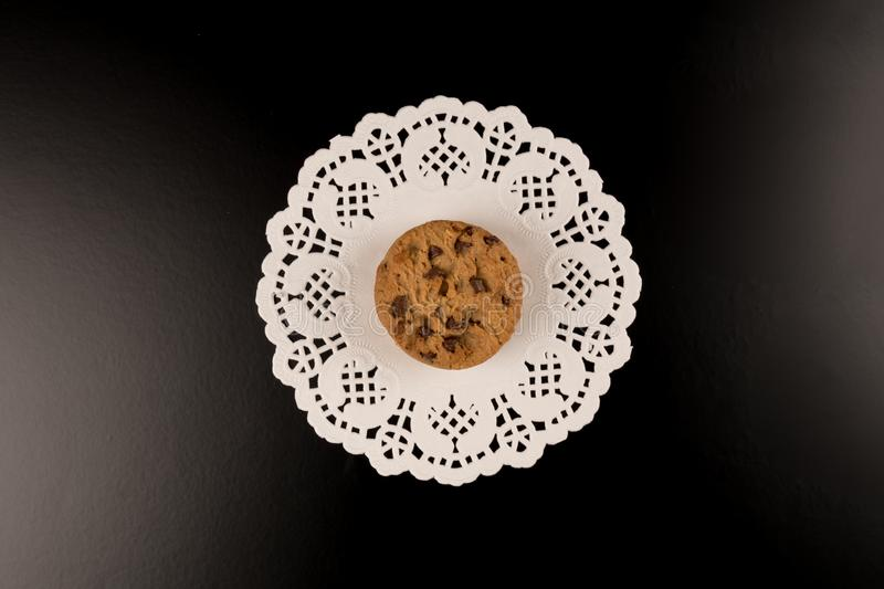 Chocolate chip cookies in beautiful white lace, black background. top view stock photo