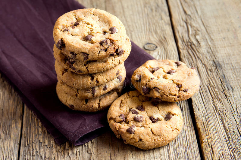 Chocolate chip cookies. On brown napkin and rustic wooden table royalty free stock photo