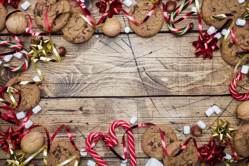 Chocolate chip cookies Christmas canes caramel red gold scenery and marshmallow on wooden background. Copy space Frame royalty free stock image