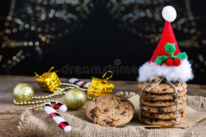 Chocolate chip cookies freshly baked are stacked with santa hat. And gift box on sackcloth and wooden table with christmas lights in the background. Homemade royalty free stock image