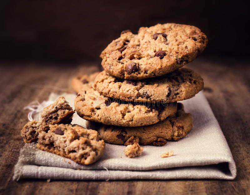 Chocolate chip cookies on linen napkin on wooden table. Stacked. Chocolate chip cookies close up royalty free stock photo