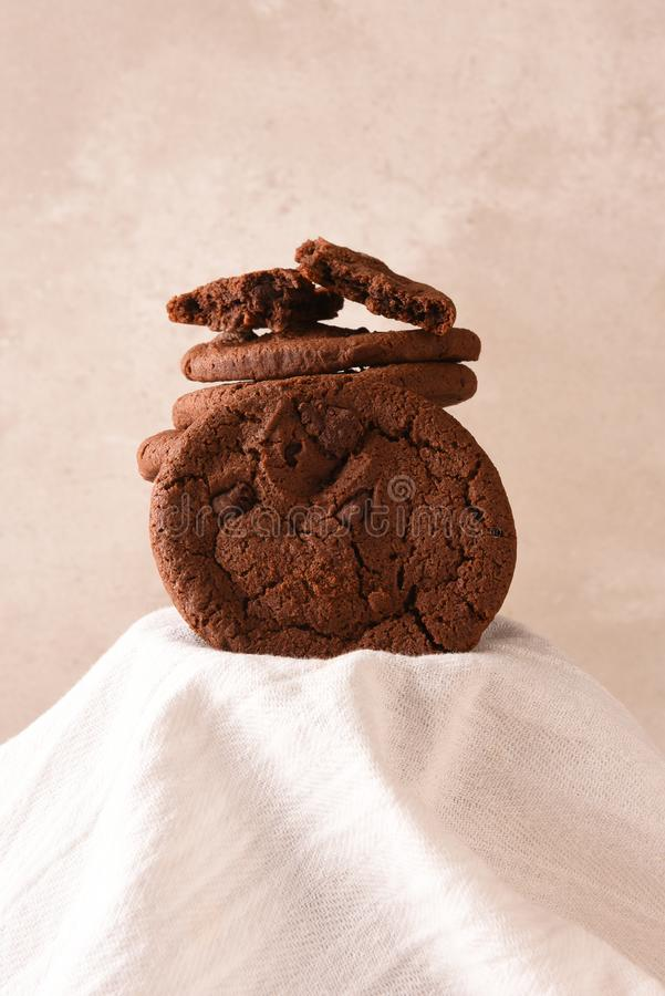 Chocolate Chocolate Chip cookies on a pedestal covered with a kitchen towel. Chocolate Chocolate Chip cookies on pedestal covered with a kitchen towel stock photo