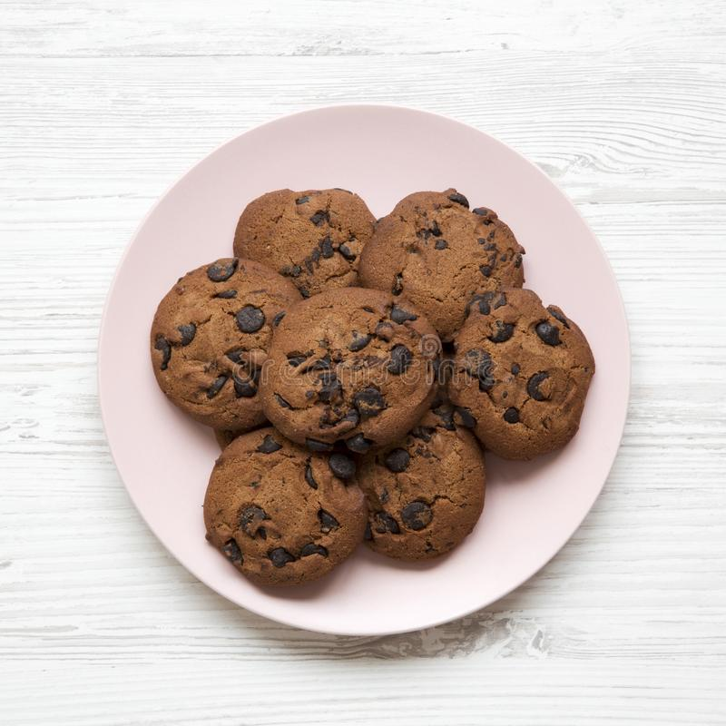 Chocolate chip cookies on a pink plate on a white wooden background. Flat lay, overhead royalty free stock photos