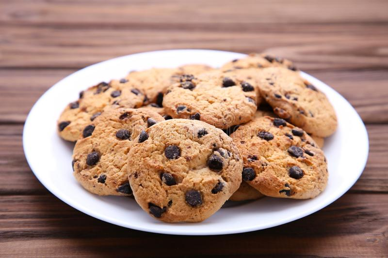 Chocolate chip cookies on plate on brown wooden background royalty free stock images