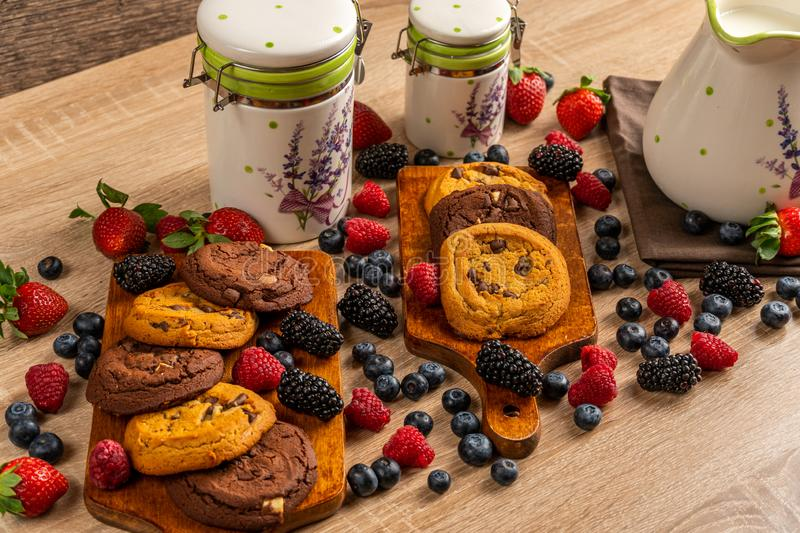 Chocolate chip cookies on wooden board assorted with mix of forest fruits with ceramic vessels stock images
