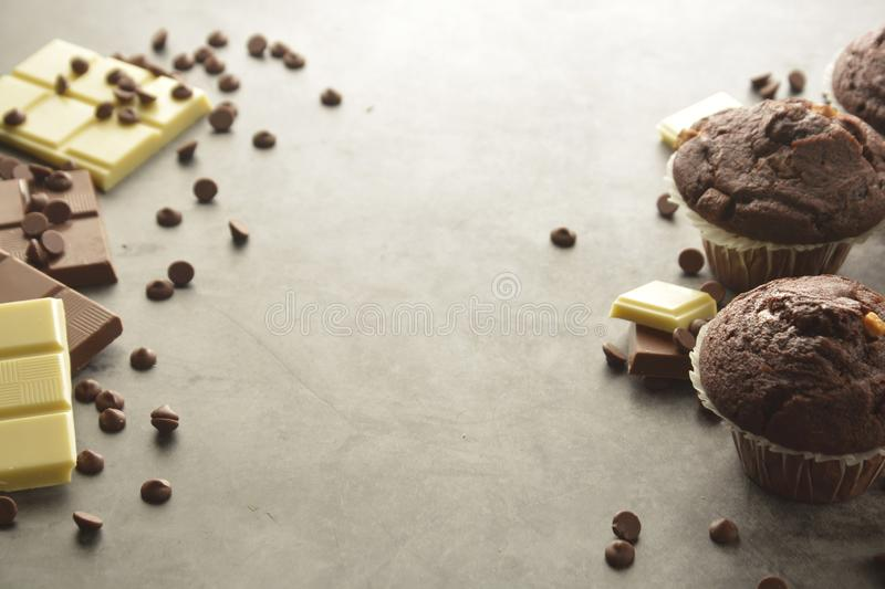 Chocolate chip muffin with chocolate bar. White and dark chocolate. Copy space. Chocolate chip muffin with chocolate bar. White and dark chocolate bars. Copy stock image