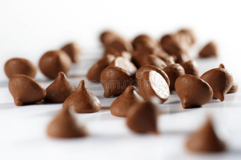 Chocolate chips. All over the white table stock photos