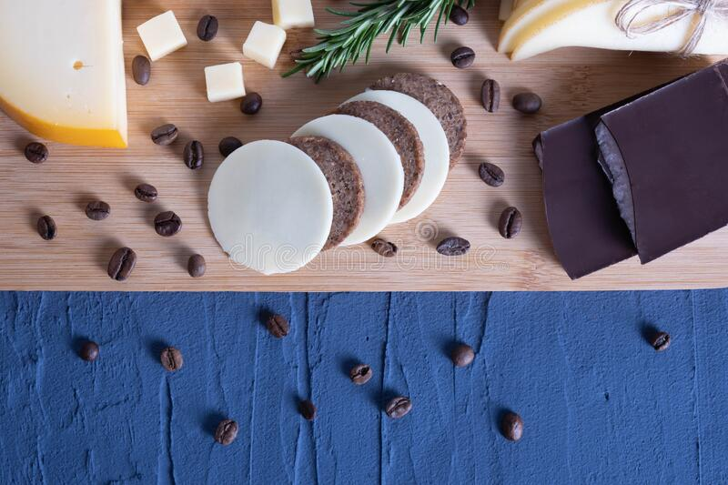 Chocolate, chopped cheese with berries. On a wooden board royalty free stock photo
