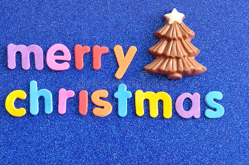 A chocolate Christmas tree with the words Merry Christmas. On a blue background royalty free stock images
