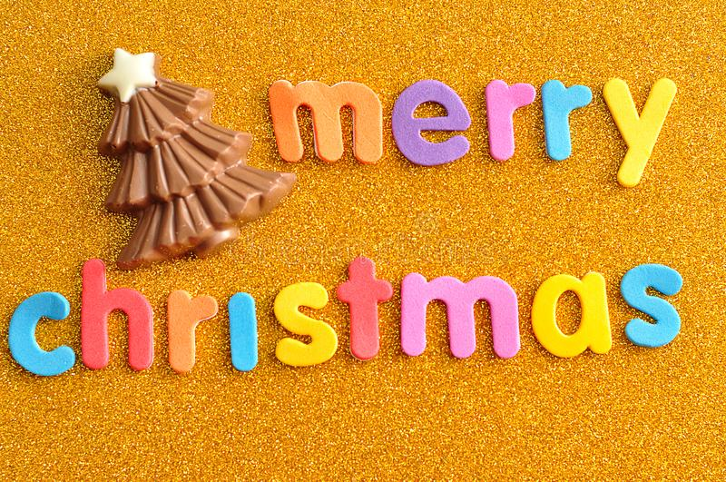 A chocolate Christmas tree with the words Merry Christmas. On a golden background stock photo