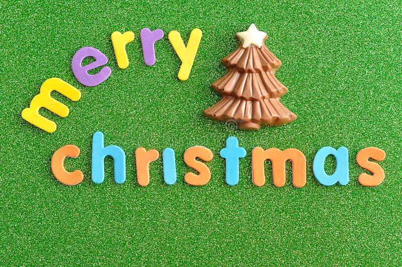 A chocolate Christmas tree with the words Merry Christmas. On a green background royalty free stock image