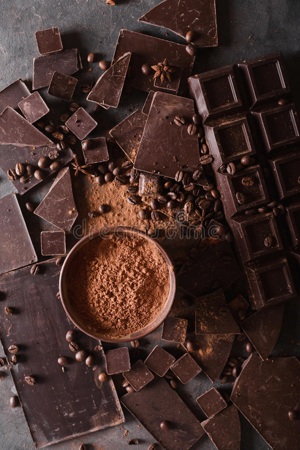 Chocolate chunks and cocoa powder. Coffee beans Chocolate bar pieces. Large bar of chocolate on gray abstract background. stock photos