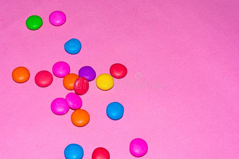 Chocolate coated candies on pink background. Rainbow colored chocolate coated candies on pink background with copy space stock photos