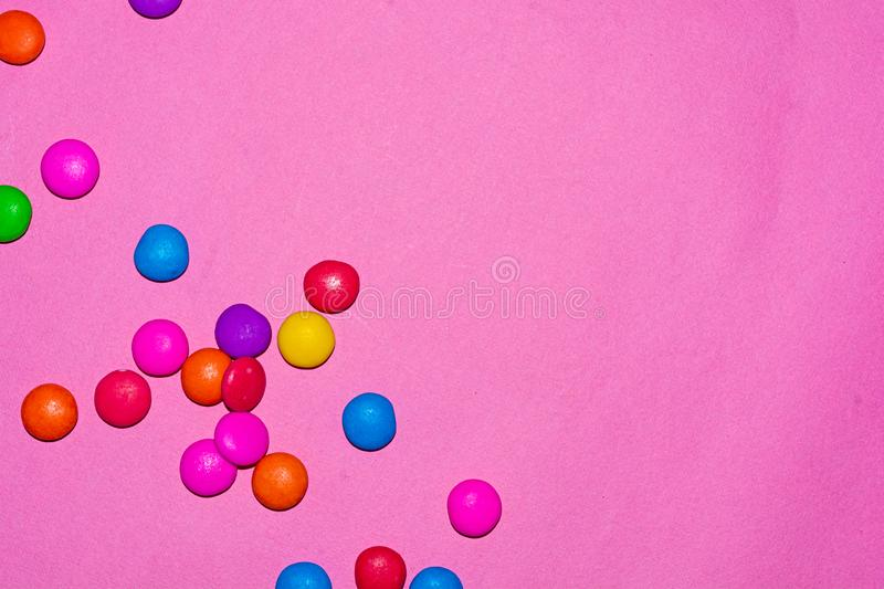 Chocolate coated candies on pink background. Rainbow colored chocolate coated candies on pink background with copy space stock photography