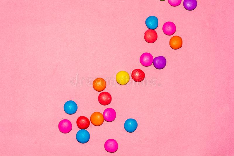 Chocolate coated candies on pink background. Rainbow colored chocolate coated candies on pink background with copy space royalty free stock image