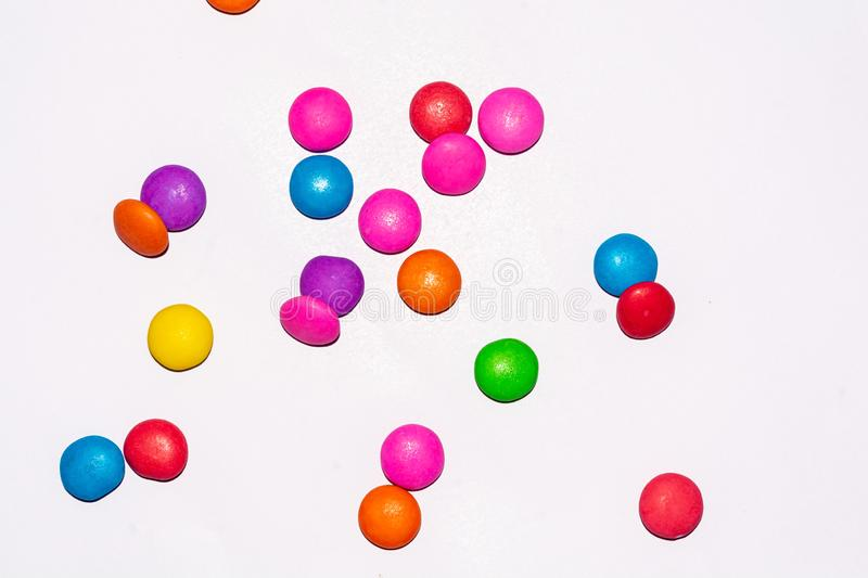 Chocolate coated candies on white background. Rainbow colored chocolate coated candies on white isolated background with copy space stock images