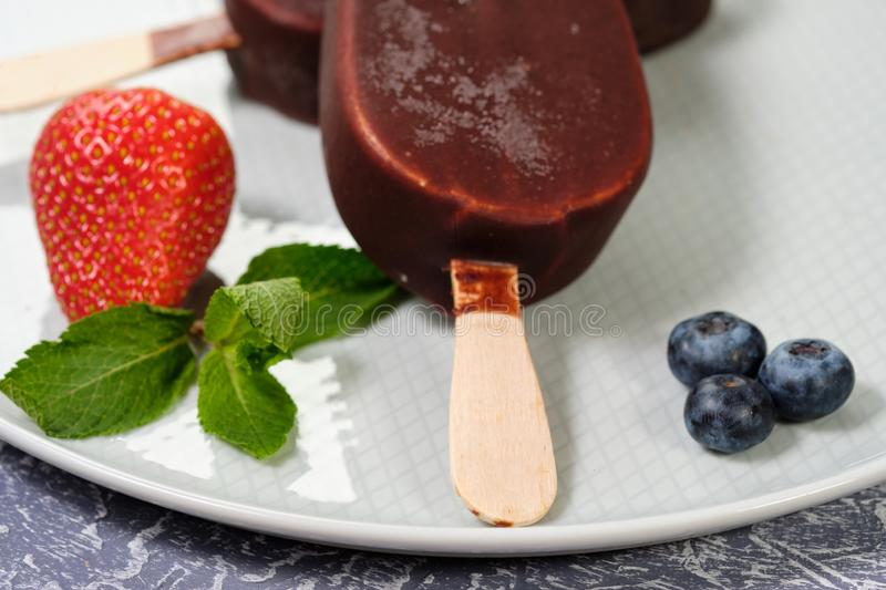 Chocolate-coated ice cream with strawberries and blueberries on a white plate close-up stock photos