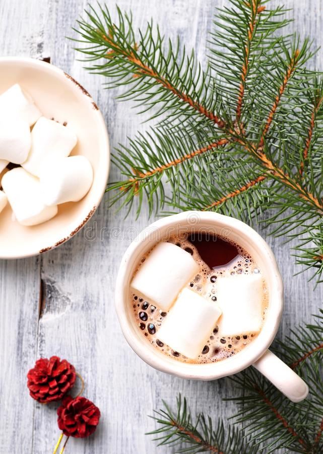 Chocolate or cocoa drink with marshmallows in a Christmas cup on the background of spruce royalty free stock photography