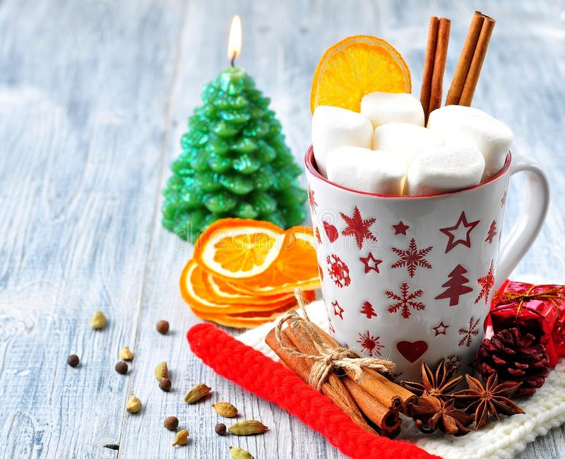 Chocolate or cocoa drink with marshmallows and cinnamon in a Christmas cup with cinnamon on gray wooden background royalty free stock photography