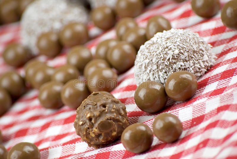 Chocolate and coconut covered marshmallow. Over red and white cloth royalty free stock images