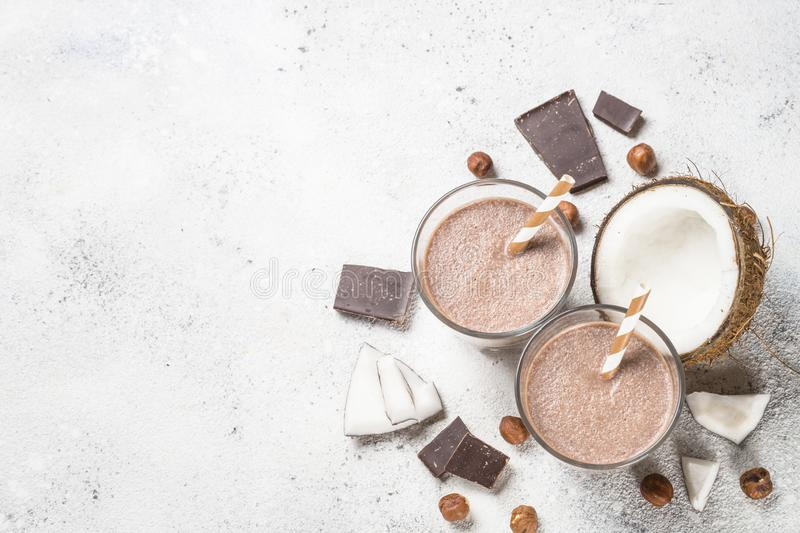 Chocolate coconut hazelnut milkshake or smoothie top view. Chocolate coconut hazelnut milkshake or smoothie in two glasses on white table. Top view with copy stock photos