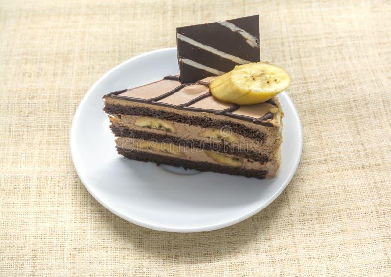 Chocolate Coffee banana cake. On white plate, bark background stock photo