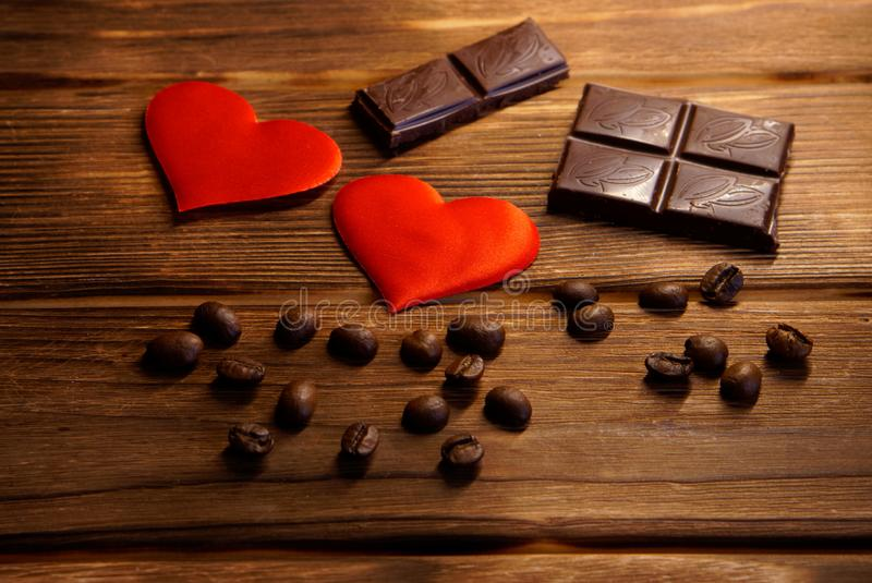 Chocolate, coffee beans and red hearts lie on a natural wooden background. Still life for lovers stock image
