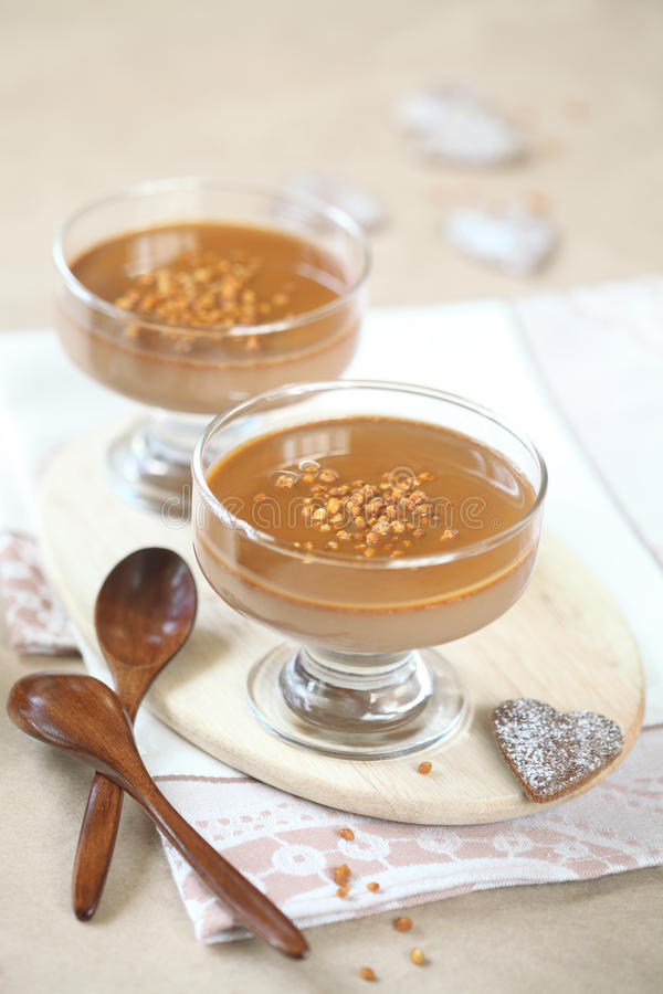 Chocolate Coffee Panna Cotta with Caramel Sauce. On a wooden cutting board, wooden spoons and chocolate cookies, on a light beige background stock photo