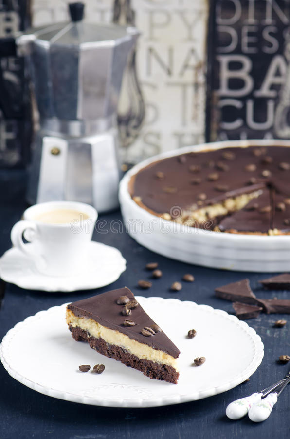 Chocolate and coffee tart. With salted caramel on a dark wooden background stock image