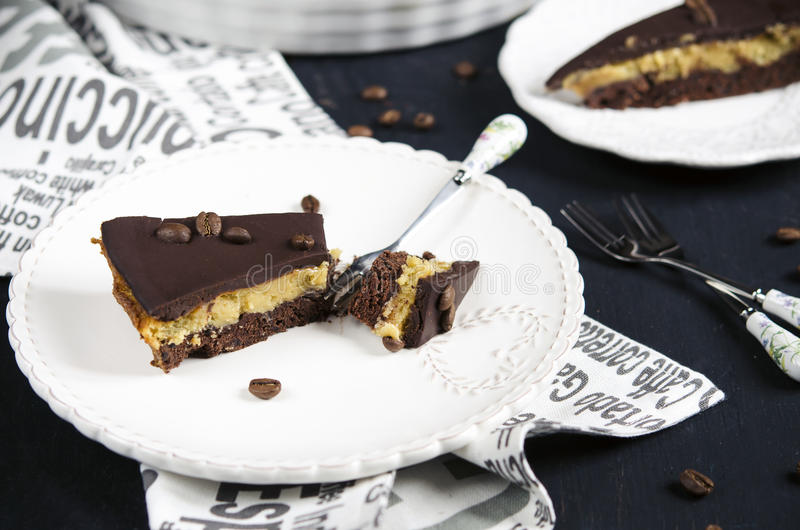 Chocolate and coffee tart. With salted caramel on a dark wooden background royalty free stock image