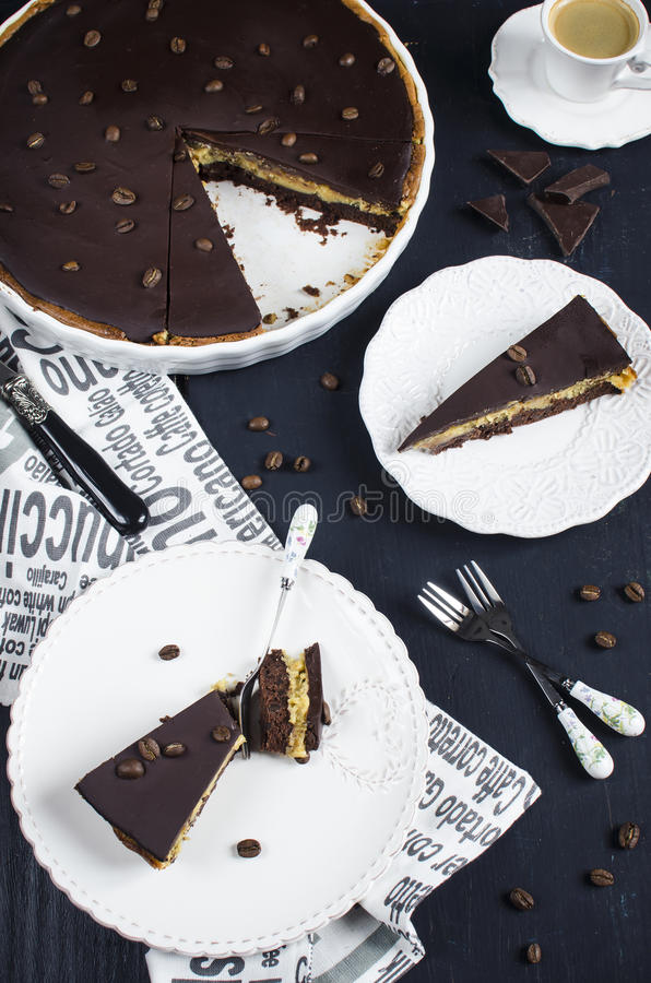 Chocolate and coffee tart. With salted caramel on a dark wooden background royalty free stock photos