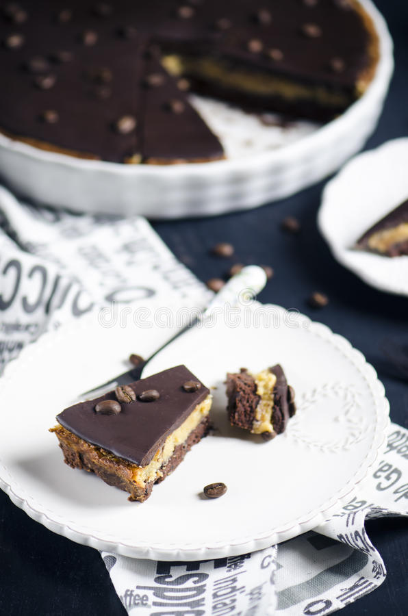 Chocolate and coffee tart. With salted caramel on a dark wooden background royalty free stock images